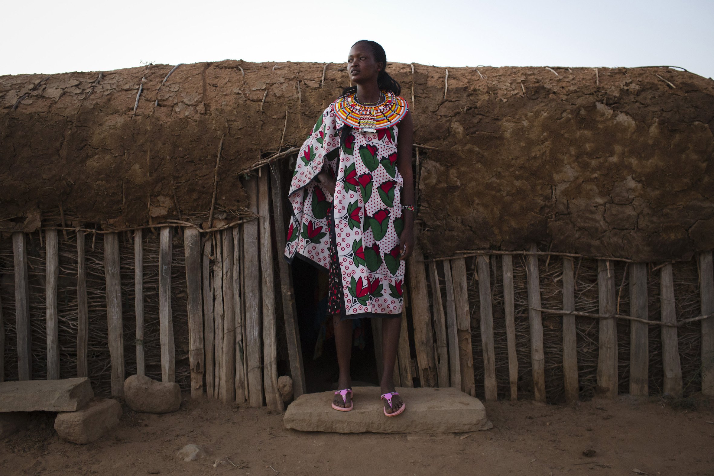 Judi Lerumbe, 21, stands by her home in the village of Umoja in Samburu, Kenya on February 19, 2015.